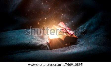 Gift box on a dark magic background with light bokeh. Festive background, magic box with a gift. Dark abstract background with gold bokeh. Royalty-Free Stock Photo #1746910895