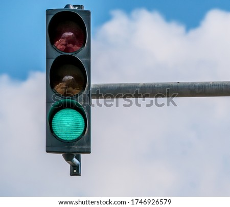 Traffic light against blue sky showing the color green.
