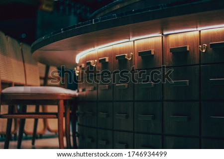 LED strip lights hidden away under a wooden counter for decorating in cafe and restaurant. dark vintage tone background. Royalty-Free Stock Photo #1746934499