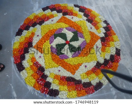 Pookalam is an intricate and colourful arrangement of flowers laid on the floor. ... 'Pookhalam' consists of two words, 'poov' meaning flower and 'kalam' means colour sketches on the ground.