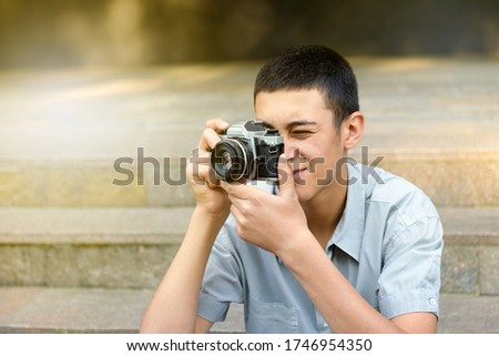 Young man taking photographs on his camera outdoors on urban steps smiling as he composes and focuses his shot