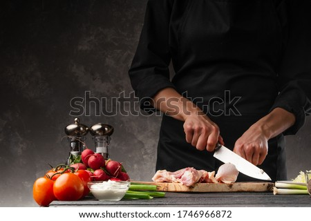 A chef cuts a chicken leg for cooking meat dishes. Cooking and cooking. Culinary blog or cooking show. #1746966872