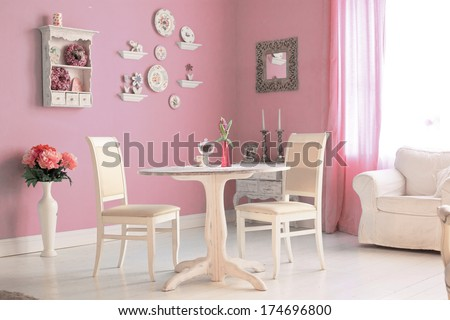 dining room interior with flowers decorative plates and pink wall