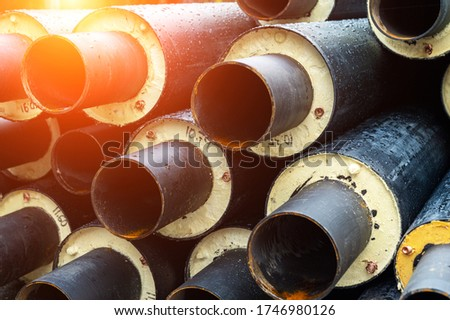 Heap of many new black insulated steel pipes at municipal construction site outdoors. Heating main district pipeline renewal or reconstruction. City development building industrial background Royalty-Free Stock Photo #1746980126