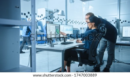 Modern Electronics Factory: Male Supervisor Talks to a Female Electrical Engineer who Works on Computer with CAD Software. Developing PCB, Microchips, Semiconductors and Telecommunications Equipment Royalty-Free Stock Photo #1747003889