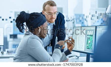 Modern Electronics Factory: Female Supervisor Talks to a Male Electrical Engineer who Works on Computer with CAD Software. Designing PCB, Microchips, Semiconductors and Telecommunications Equipment #1747003928