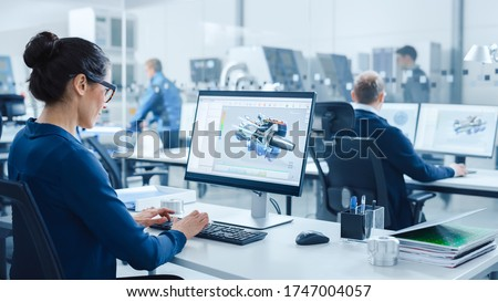 Industrial female Engineer Working on a Personal Computer, Screen Shows CAD Software with 3D Prototype of Electric Engine. In Background Modern Factory with High-Tech CNC Machinery #1747004057