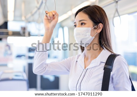 Asian business woman wear surgical mask face to protect herself while commuting in the metro or train #1747011290