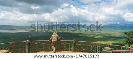 A single Tourist looks into the Ngorongoro Conservation Area with the Lake Magadi from the Look Out.  Beautiful landscape scenery in Tanzania, Africa, Panorama view with Clouds and Rain  Royalty-Free Stock Photo #1747015193