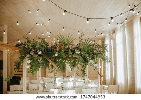 Restaurant, served table, rustic, huge compositions of flowers and tropical leaves on the table, plates, cutlery, crystal glasses, wooden chairs, garlands of light bulbs.