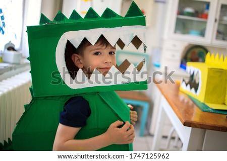 Smiling boy wearing a cardboard dinosaur costume  Royalty-Free Stock Photo #1747125962