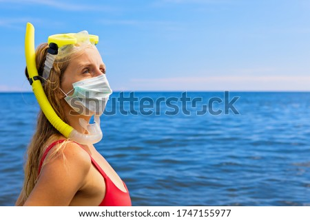 Girl in snorkeling mask wear surgical face mask on sea beach. Cancelled cruises, tours due coronavirus COVID 19 world epidemic. Travel ban for family vacation, tourism industry crisis at summer 2020