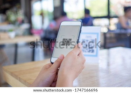 Women's hands are using  the phone to scan the qr code to select food menu. Scan to get discounts or pay for food. The concept of using a phone to transfer money or paying money online without cash. #1747166696