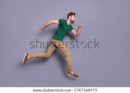 Full size profile side photo of anxious guy jump run fast afraid miss spring season discounts wear casual style clothes isolated over gray color background