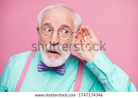 Closeup photo of attractive grandpa hand near ear listen rumors focused chatterbox bad person wear specs mint shirt suspenders violet bow tie isolated pink pastel color background #1747174346