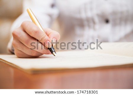 Hand pointing with pen to music book with handwritten notes #174718301