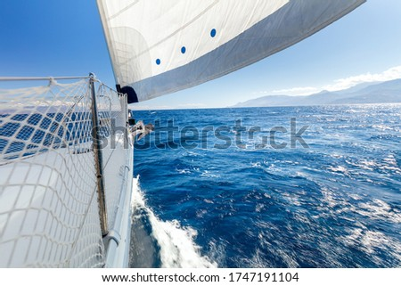 Sail boat, Sailing with fresh speed wind. A view from the yacht's deck to the bow and sails. Sail boat with set up sails gliding in open sea. Greece, Europe #1747191104