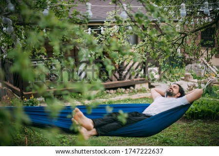A man is resting in a hammock in a country house. A young guy lies in a hammock, dozing outdoors in the summer in the green of trees in the country #1747222637