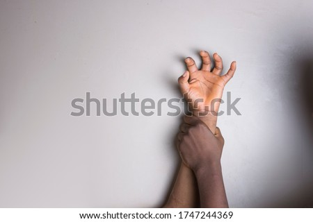 Hand of a young African girl being paped and the hand of the rapist.  #1747244369