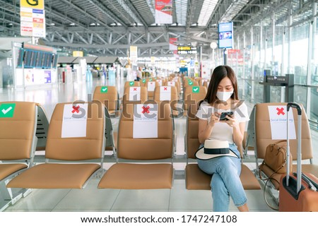 Asian female tourist wearing mask using mobile phone searching airline flight status and sit social distancing chair in airport during coronavirus or covid-19 virus outbreak a new normal concept #1747247108