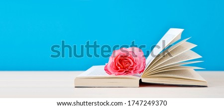 "open book with nostalgic Hybrid Tea ""Augusta Luise"" rose flower on blue background. reading, education, literature, learning and back to school concept. copy space. close-up, panoramic picture"