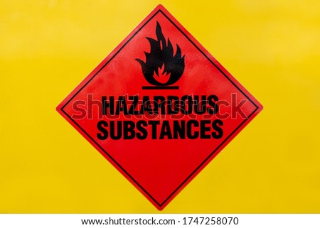 Red Hazardous Substances sign on a yellow cabinet front