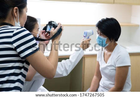 young asian woman who is a stock photographer using camera to shoot picture of doctor measuring temperature of patient. stocker job and freelance concept