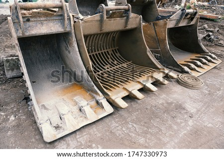 Large used excavator shovels stand side by side on a cement floor. Royalty-Free Stock Photo #1747330973