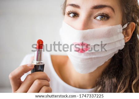 portrait of young woman wearing medical face mask during coronavirus. Make up problem and epidemy. Red lipstick on the protection mask.  #1747337225