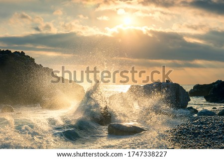 Big Wave hit the rock at beach, sea water splash up to the sky with sun. Sunset Sundown at Sea. Storm. Seascape. Royalty-Free Stock Photo #1747338227