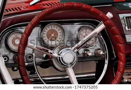 Part of the interior of an oldtimer sports luxury car with steering wheel, speedometer, fuel, clock dials, gear lever, front panel. #1747375205