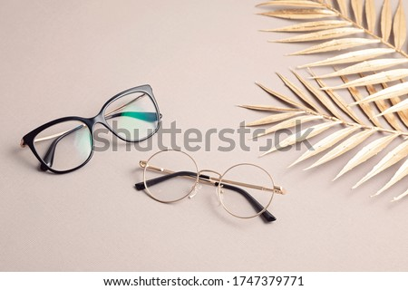Stylish eyeglasses over pastel  background. Optical store, glasses selection, eye test, vision examination at optician, fashion accessories concept. Top view, flat lay Royalty-Free Stock Photo #1747379771