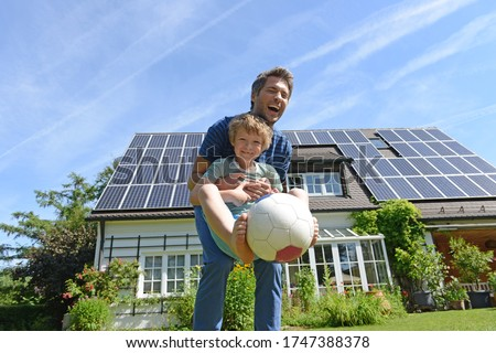 Father and son playing with ball in garden of solar paneled house Royalty-Free Stock Photo #1747388378