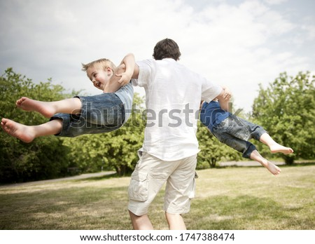 father spinning son's around in park #1747388474