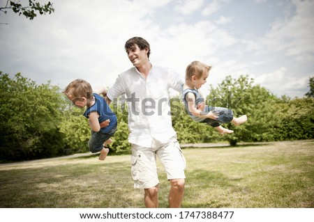 father spinning son's around in park Royalty-Free Stock Photo #1747388477