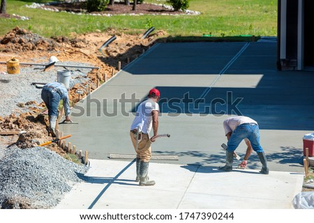 Unidentifiable hispanic men working on a new concrete driveway at a residential home #1747390244