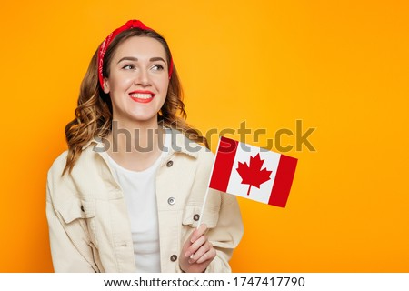 Young happy girl student smiling and holding a small canada flag and looking away isolated over orange background, Canada day, holiday, confederation anniversary, copy space #1747417790