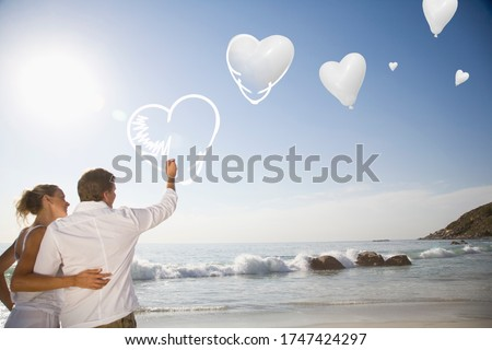 Couple drawing digital hearts in sky at beach #1747424297