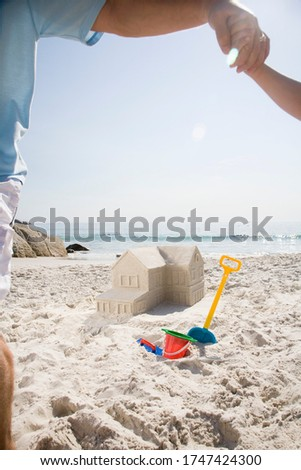 Father and son building sandcastle shaped like house #1747424300