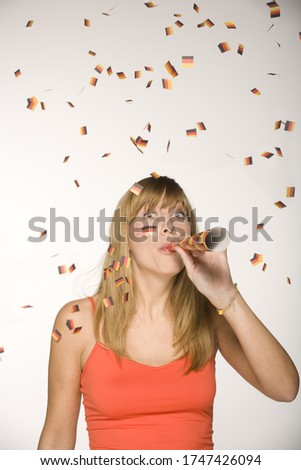 Young woman blowing in noisemaker #1747426094