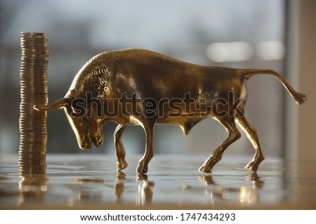 Stack of One Euro coins next to bull figurine #1747434293