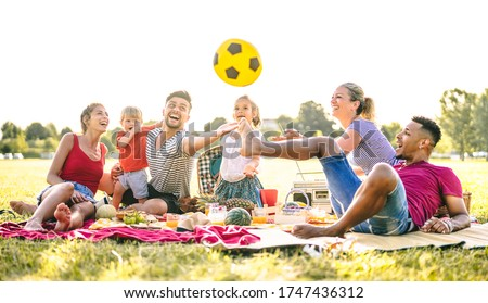 Happy multiracial families having fun with cute kids at pic nic garden party - Multicultural joy and love concept with mixed race people playing together with children at park - Bright sunny filter