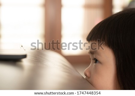 Asian girl watching a scary cartoon online from a notebook computer, which has a facial expression and a bright expression of fear and concern.
