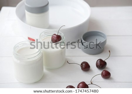 homemade organic yogurt in glass jars in yogurt maker. automatic yogurt machine to make fermented milk product at home. yogurt or kefir making during quarantine concept. cherries near glass jars. #1747457480