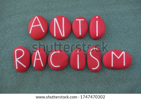 Anti Racism, social issue slogan text composed with red colored stone letters over green sand Royalty-Free Stock Photo #1747470302