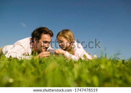 Father and daughter looking at grass #1747478519