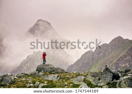 Hiker with camera standing on top of a mountain and enjoying landscape. High Tatras mountains. Landscape photographer photographs a mountain view.