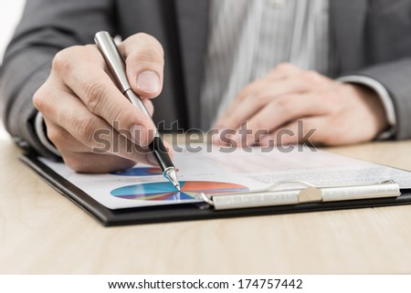 Businessman's hand showing financial report on table #174757442
