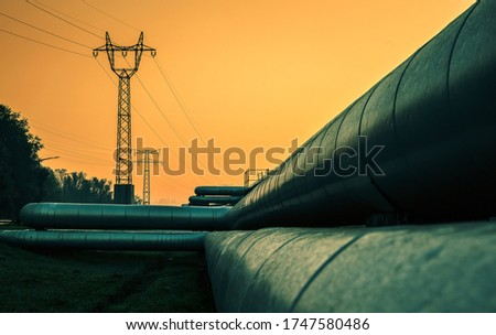 Electric wires and district heating tubes at sunrise Royalty-Free Stock Photo #1747580486