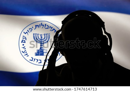 A dark silhouette of a man with headphones listening, Israeli intelligence, spy and special agent, the Israeli flag of the special services. Hebrew inscription, menorah Image, selective focus.